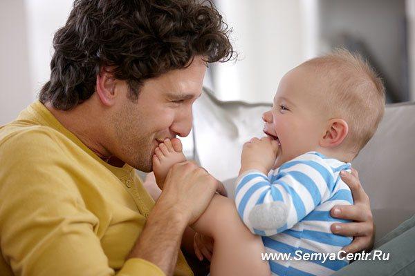 Отец целует пальчики маленького сына