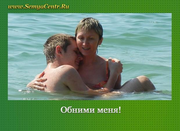 Женщина держит в воде взрослого сына на руках