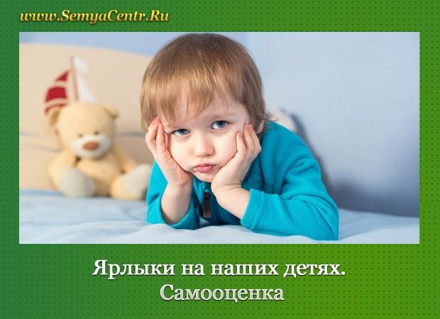 Ребёнок в бирюзовой рубашке держит руками подбородок. На заднам фоне бежевй мишка